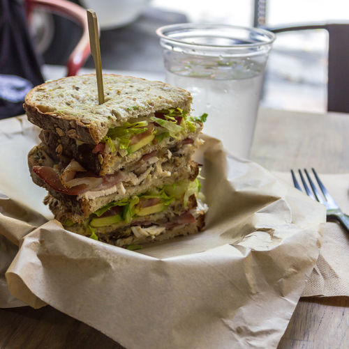 Triple decker Club sandwich in Miami Close-up Day Food Food And Drink Freshness Healthy Eating Indoors  Lettuce No People Plain Brown W Ready-to-eat Sandwich Serving Size Table TripleDeckerClub Water Glass Wholegrain Bread