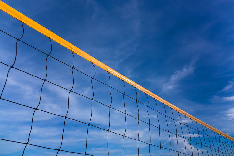 Low angle view of beach volleyball net against blue sky