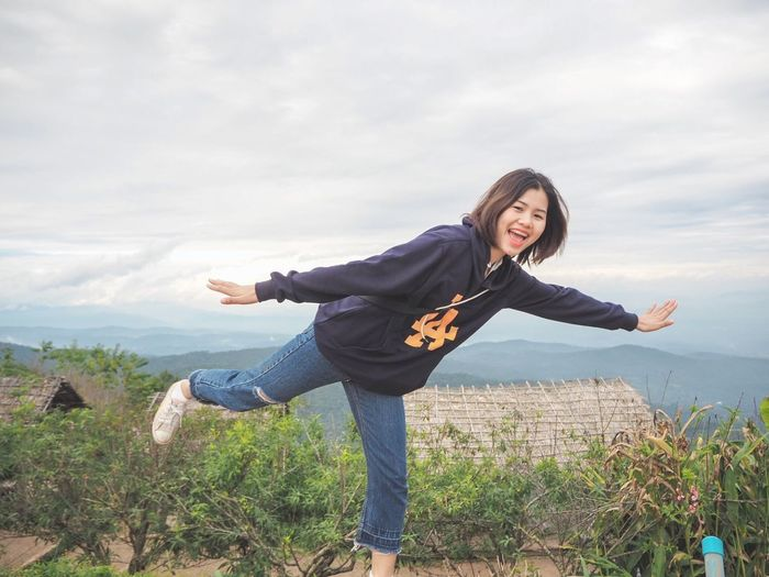 Full length of happy young woman with arms raised against sky
