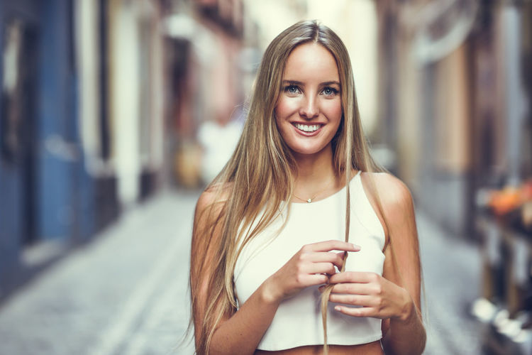 Young woman smiling in urban background. Blond girl with straight hairstyle wearing casual clothes in the street. Architecture Beautiful Woman Beauty Casual Clothing City Drink Drinking Emotion Focus On Foreground Food And Drink Front View Hair Hairstyle Happiness Holding Looking At Camera One Person Outdoors Portrait Smiling Standing Young Adult Young Women