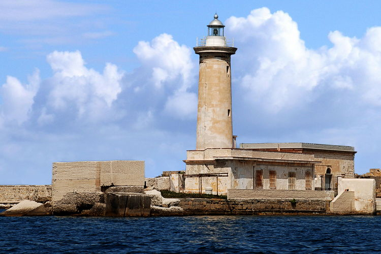 Lighthouse in sea at marsala against sky