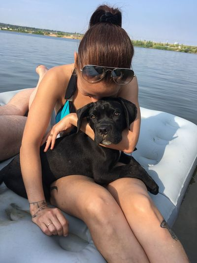 Midsection of woman with dog sitting in water