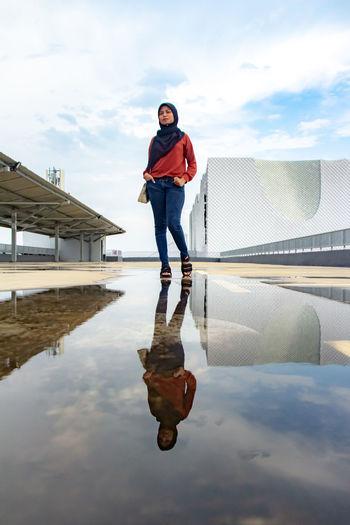 Full length of woman standing by puddle against sky