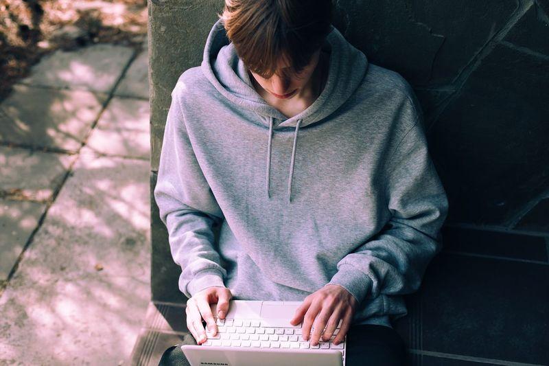 Full length of teenage girl sitting on mobile phone