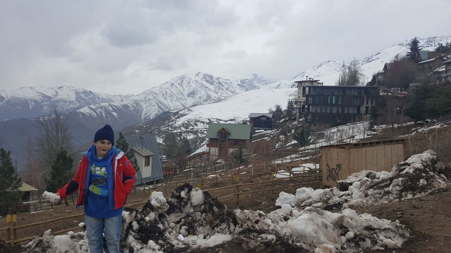 Boy Holding Snow Against Mountain In Town