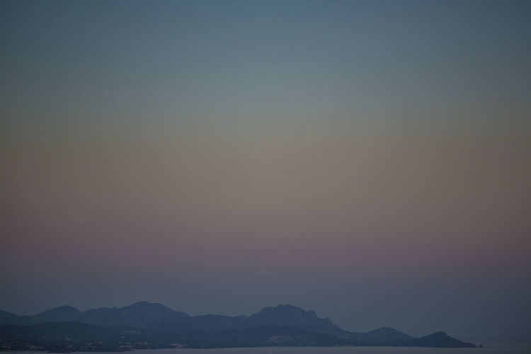 Scenic view of silhouette mountains against sky during foggy weather