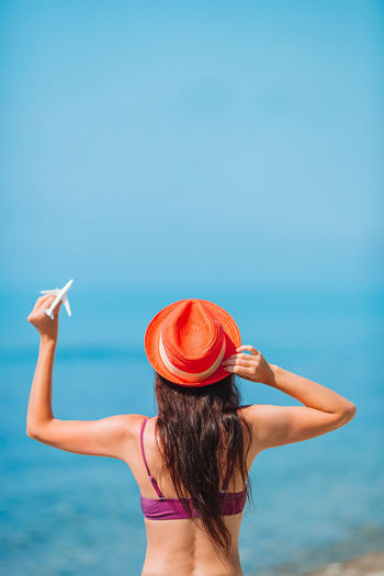 Rear view of woman walking in sea against sky