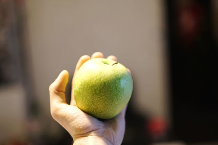 Cropped Hand Holding Granny Smith Apple At Home