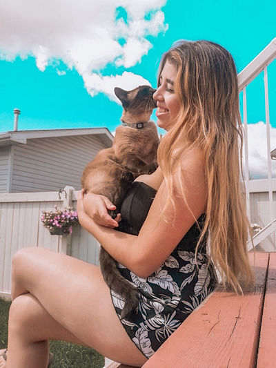 Midsection of woman with dog sitting outdoors