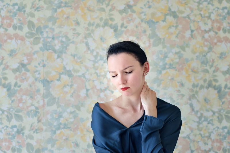 Young Woman With Eyes Closed Standing Against Wallpaper