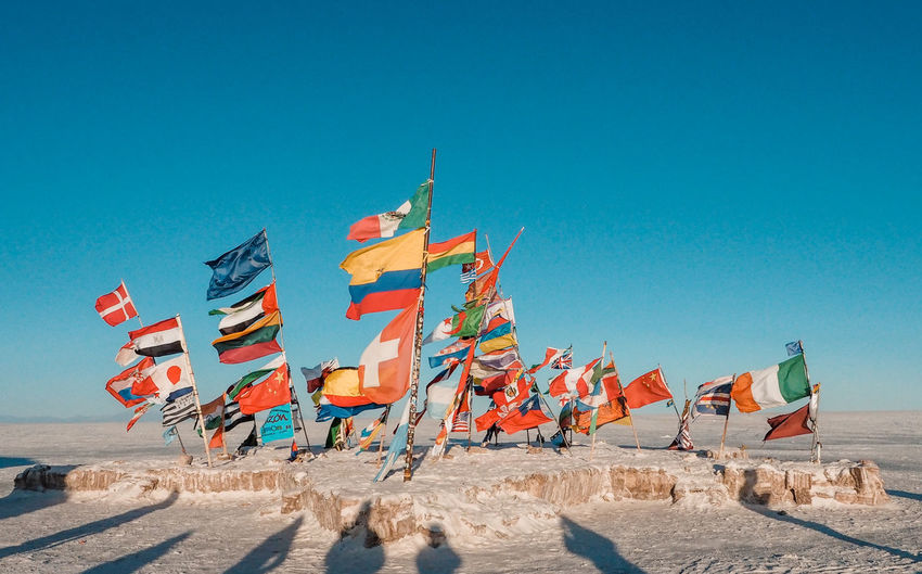 Flags of the world on the salt flats Architecture Beach Blue Clear Sky Copy Space Day Environment Flag In A Row Land Multi Colored Nature No People Outdoors Sand Scenics - Nature Sky Sunlight Sunny Wind