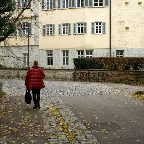 Rear view of woman walking on street against buildings