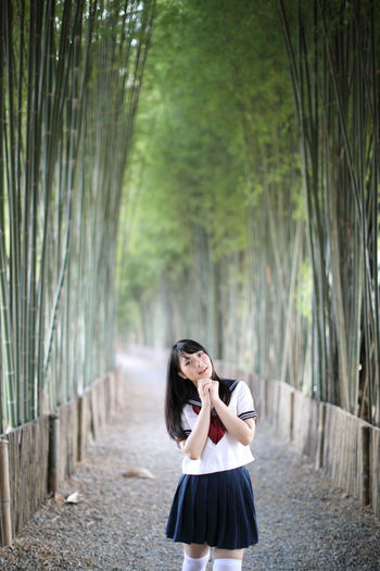 Portrait of young woman while standing amidst bamboo groove