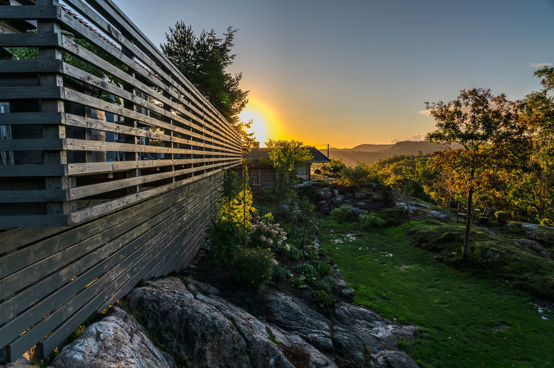 Sunset Plant Tree Sky Nature Sunset No People Building Exterior Built Structure Outdoors Rock Scenics - Nature Growth Wood - Material Rock - Object Beauty In Nature Cabin Flowers