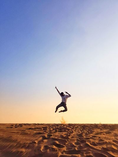 Man jumping in desert against sky during sunset