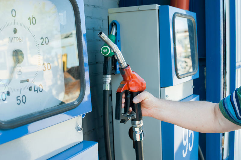 Cropped Image Of Man Holding Fuel Pump At Gas Station