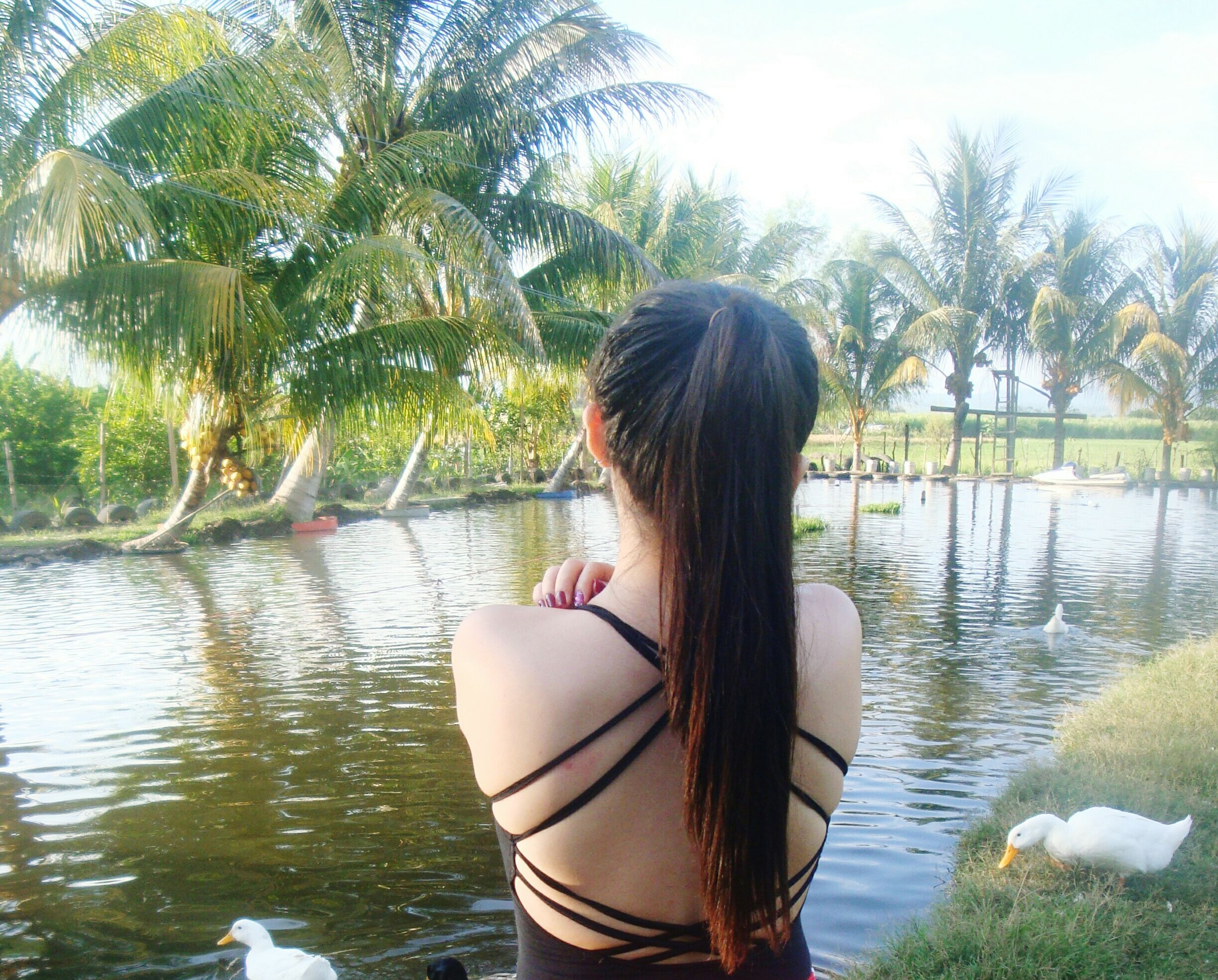 tree, real people, water, waist up, one person, lifestyles, nature, vacations, day, palm tree, beauty in nature, young adult, scenics, leisure activity, sea, outdoors, young women, sky, adults only, people, adult