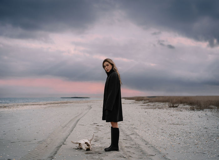 Young woman in raincoat on the beach
