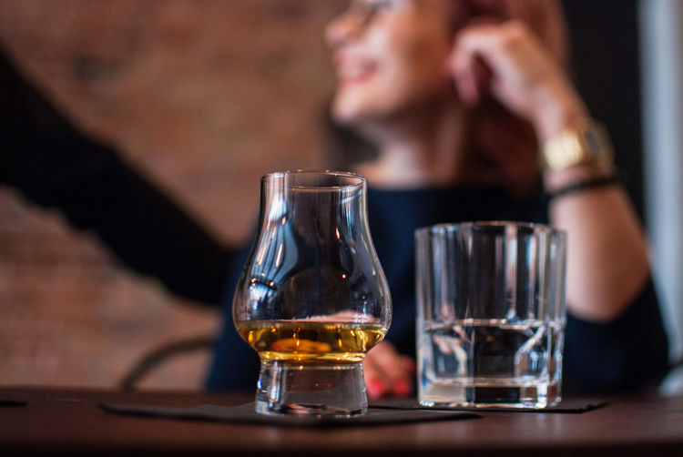 Close-Up Of Scotch Whiskey In Glass With People In Background At Bar