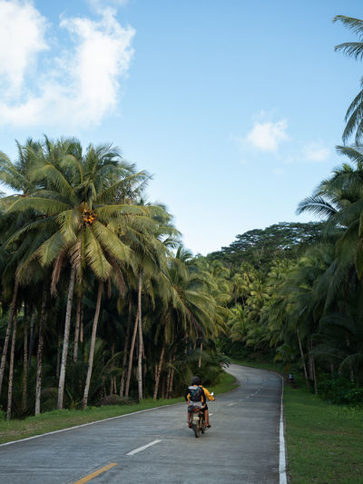 Couple riding a motorbike on Siargao Island, the Philippines. Philippines Siargao Siargao Island Motorbike Yellow Tropical Climate Tree Plant Sky Road Nature Travel Riding Cloud - Sky