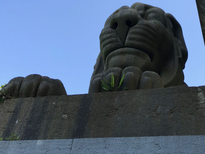 """One of the four lions """"guarding"""" the railway link between the mainland and the island of Anglesey on the Britannia Bridge. Llanfairpwllgwyngyllgogerychwyrndrobwllllantysiliogogogoch Britannia Bridge Day History Low Angle View No People Sculpture Sky Statue Of Lion"""