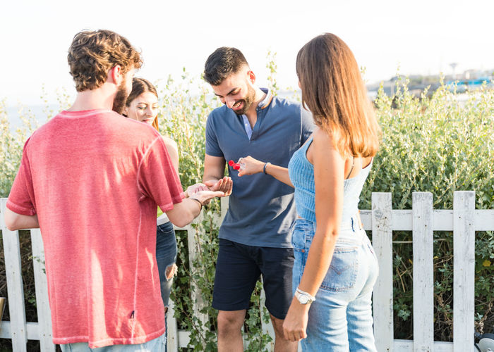 Smiling friends using hand sanitizer outdoors
