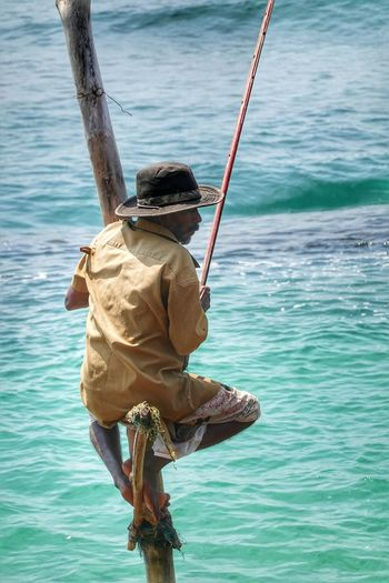 Rear view of man fishing in sea