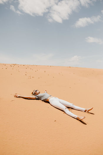 Woman lying down on desert in sunny day