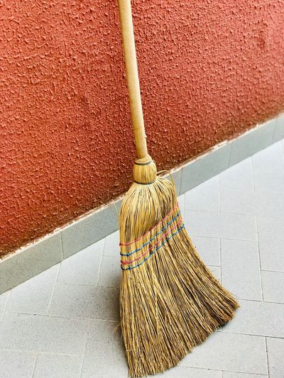 High angle view of broom on tiled floor against wall