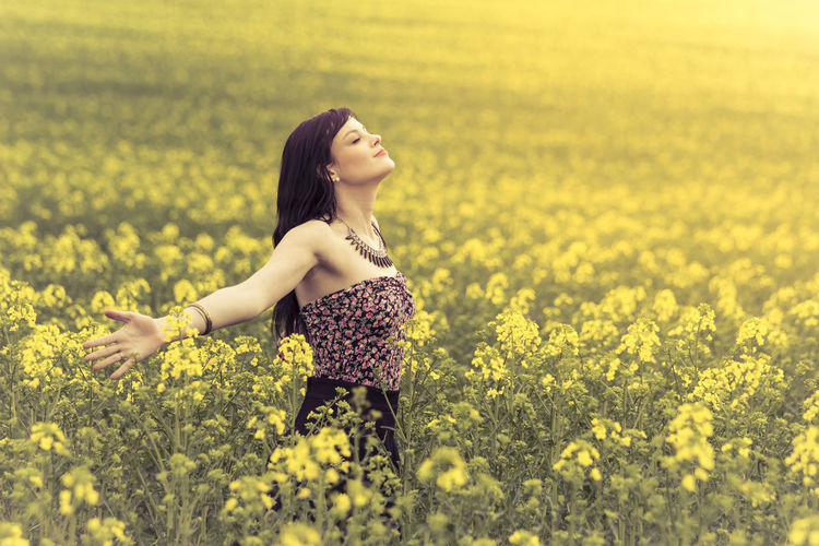 Happy positive woman in sunny summer love of youth freedom. Attractive genuine young girl enjoying the warm summer sun in a wide green and yellow meadow. Copyspace in the right. Agriculture Childhood Copyspace Dream Dreaming Flower Free Freedom Girl Happy Horizon Innocence Life Love Meadow Nature Peace Person Power Summer Sun Wellness Woman Yellow Youth