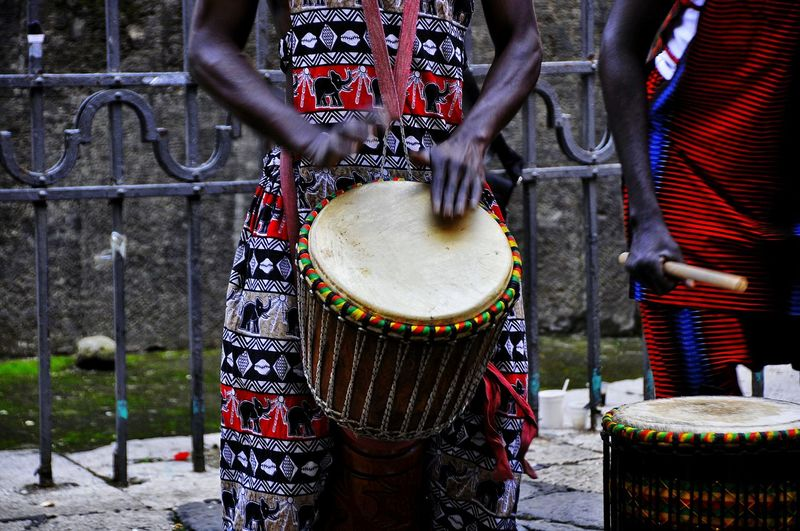 Midsection Of Street Performers Playing Bongo
