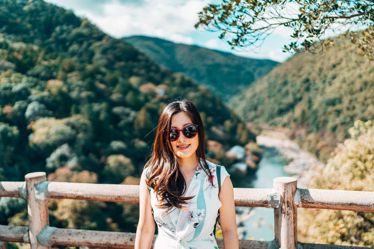Portrait of smiling young woman in sunglasses against mountains