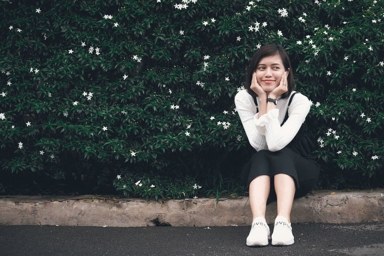 Smiling young woman looking away while sitting on footpath against plants