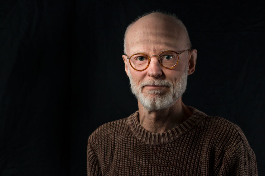 portrait of mature man adult expressive Adult Adults Only Beard Black Background Close-up Eyeglasses  Filtered Light Front View Headshot Looking At Camera One Man Only One Person Only Men People Portrait Real People Studio Shot Sweater Venetian Blinds Window Light