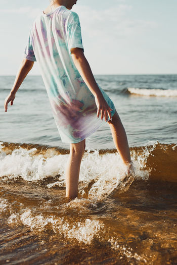 Girl spending a free time enjoying the sea and a beach at sunset during summer vacation