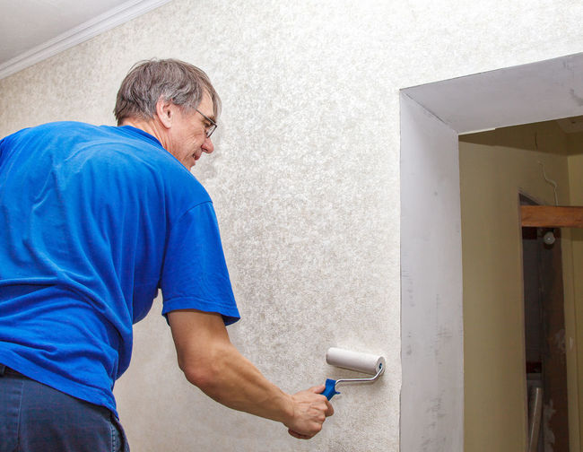 Man painting wall at home