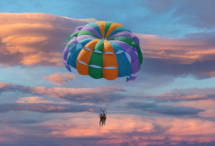 Low angle view couple flying against sky during sunset