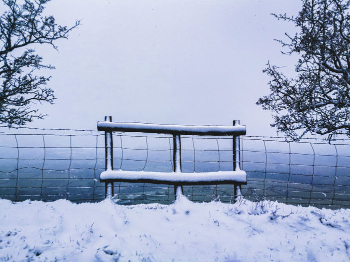 Empty bench on snow covered field during winter