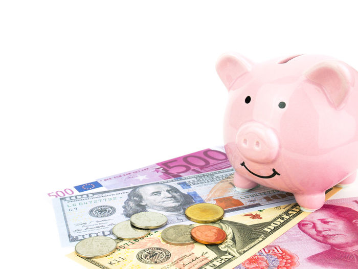 Close-up of piggy bank with currencies against white background