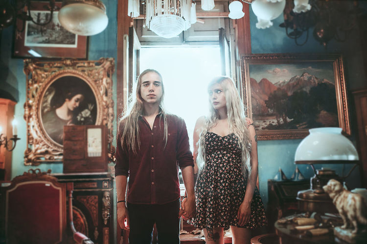 3/3 Antique Couple Blond Hair Casual Clothing Day Front View Indoors  Lifestyles Looking At Camera Portrait Real People Standing Togetherness Two People Young Adult Young Women