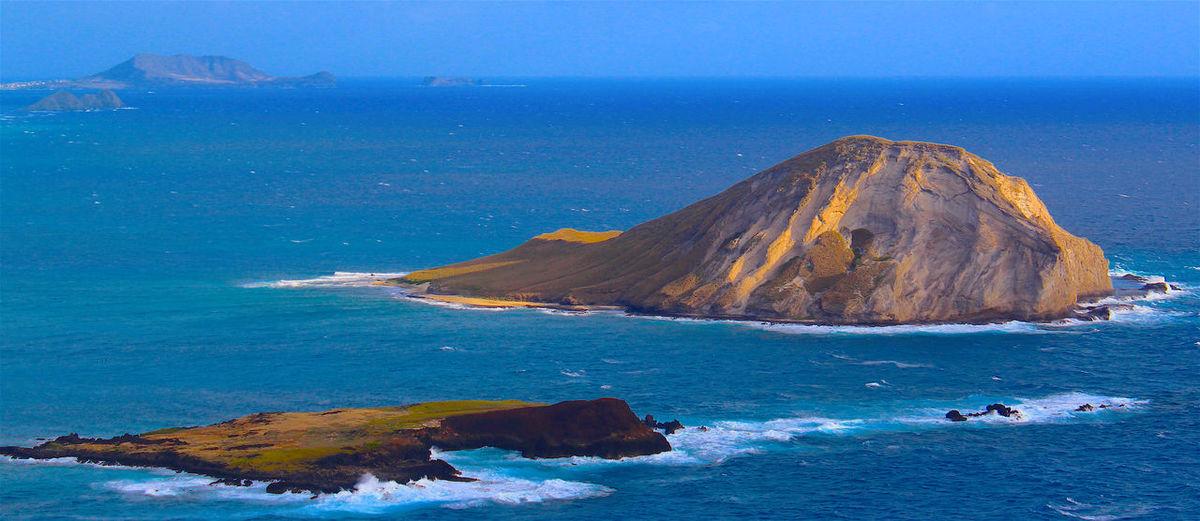Panoramic shot of headland in calm blue sea