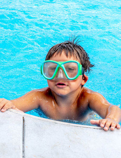 Young boy in swim goggles hangs on to the side of a in-ground pool