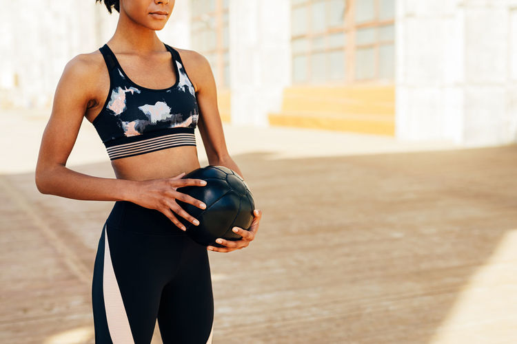 Midsection Of Young Woman Holding Ball While Standing Outdoors