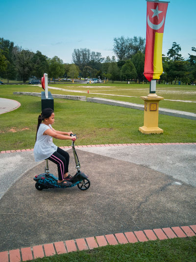 Girl riding bicycle on park against sky