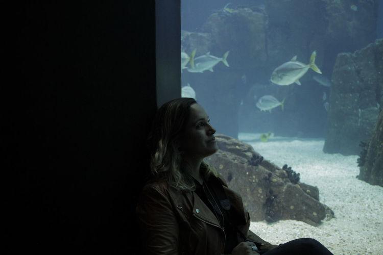 Woman looking fish in tank at aquarium