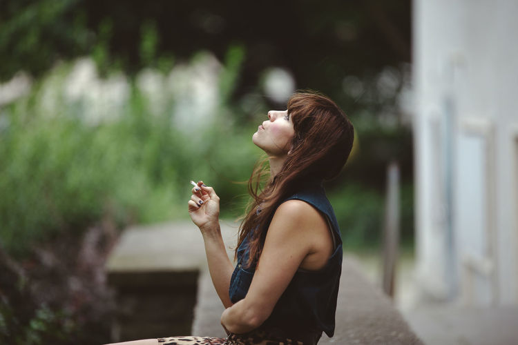 Alone Backyard Sitting Smoking Thinking Day Exhale Focus On Foreground Leisure Activity Lifestyles Long Hair One Person One Woman Only Outdoors Real People Street Photography Summer Thinking About Life Thoughtful Urban Women