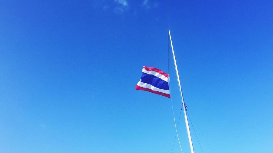 Low angle view of thai flag against clear blue sky