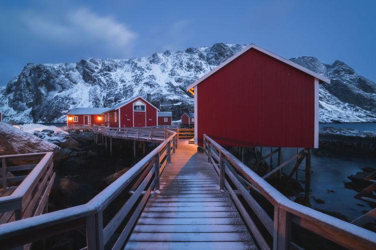 Footbridge by building against sky during winter