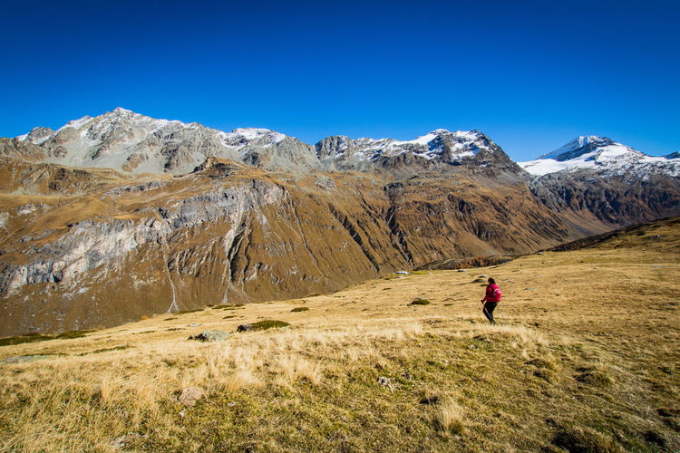 Rear view of a young woman hiking in autumn in the alps Autumn Adult Adventure Alps Beauty In Nature Day Hiking Landscape Leisure Activity Lifestyles Lone Mountain Mountain Peak Mountain Range Nature One Person Outdoors People Scenics Sky Snow Sport Switzerland Young Women