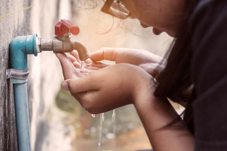 Cropped image of teenage girl drinking water from faucet